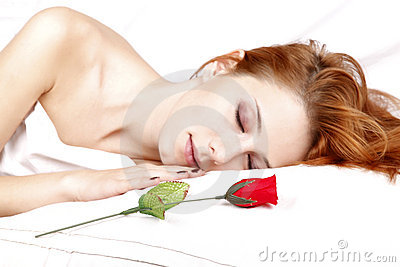 Red rose near pretty red-haired sleeping woman