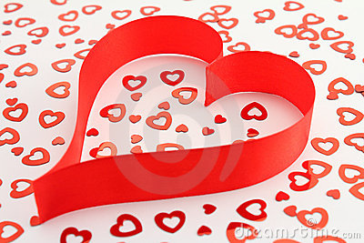 Red satin ribbon heart with heart-shaped confetti