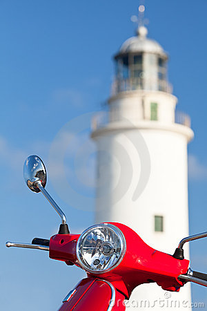 Red scooter parked near a lighthouse.