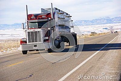 Red semi truck on winter road