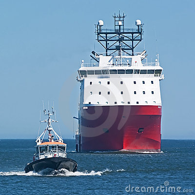Red ship with pilot boat