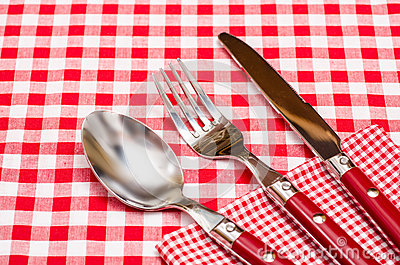 Red silverware on a red checkered napkin