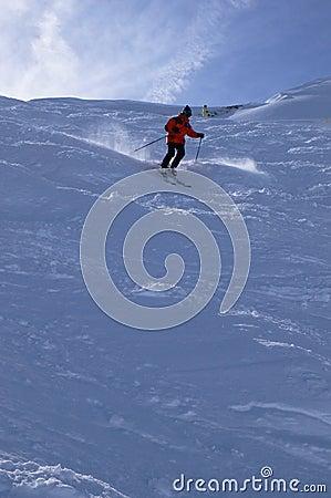 Red skier in powder snow,