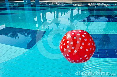 Red spotted beach ball in the swimming pool