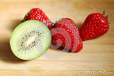 Strawberry and kiwi on chopping board