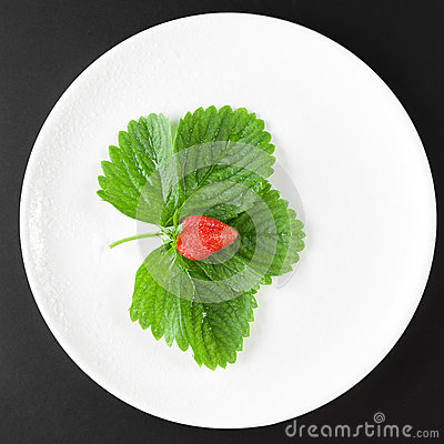 Strawberry with leaves on the white plate