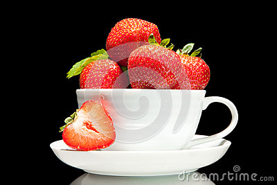 Red strawberry in white cup on a black background