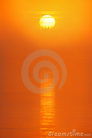 Red sun is rising in the morning mist