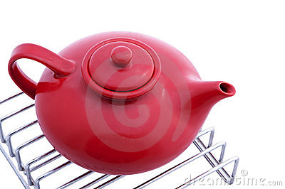 Red teapot on stainless grill