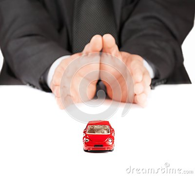 Red toy car in front of businessman, concept for insurance, buying, renting, fuel or service and repair costs