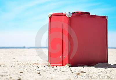 Red Travel Suitcase on Sunny Beach