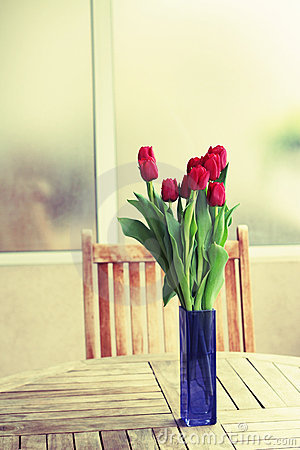 Red tulips on terrace table