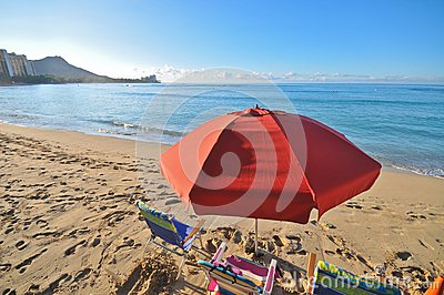 Red umbrella in beach with chairs by ocean