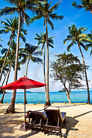 Red umbrella and chairs on sand beach in tropic