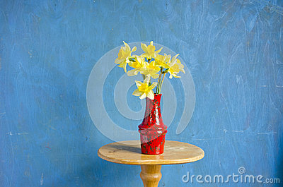 Red vase with spring narcissus on table