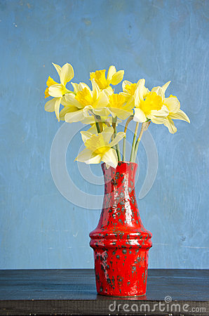 Red vase on table with spring narcissus