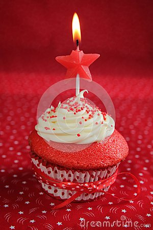 Red velvet cupcakes witht a star candle on a red background.