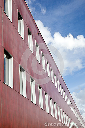 Red wall of office building and clouds