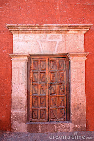 Red wall with old decorative stonedoor.