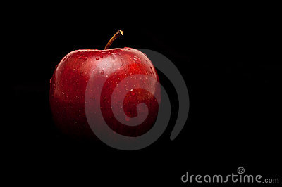 Red, wet apple on black