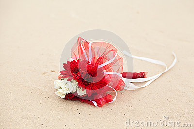 Red and white flowers wedding bouquet on sand