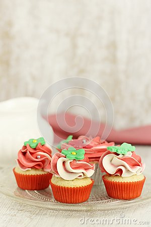 Red and white vanilla cupcakes and mini cupcakes on a plate