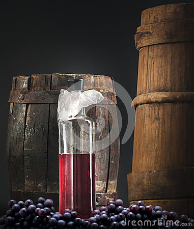 Wine bottle with grapes and barrel