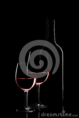 Red wine bottle and two wine glasses on black background on blac