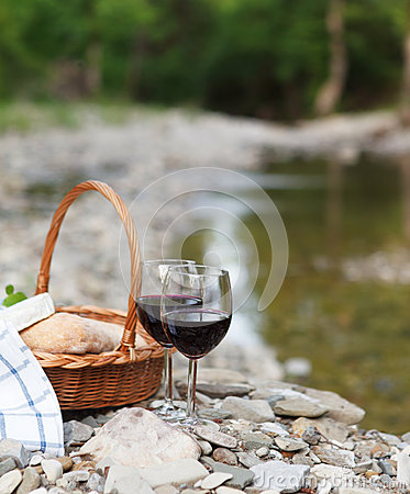 Red wine, cheese and bread served at a picnic