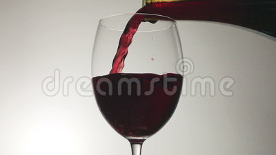 Red Wine Pouring into Glass from a Bottle. Red wine poured into a glass from a bottle, set against a moody, white / gray background stock footage