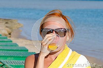 Red woman drinking orange juice