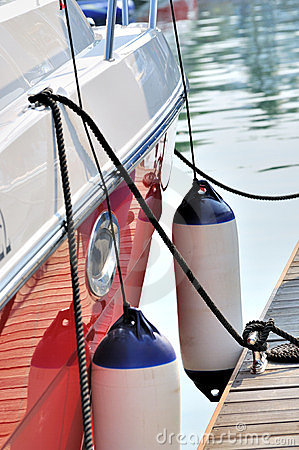 Red yacht anchoring in quiet harbor