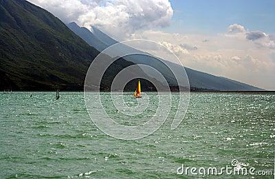 Red and Yelow Sail Windsurfer on a lake