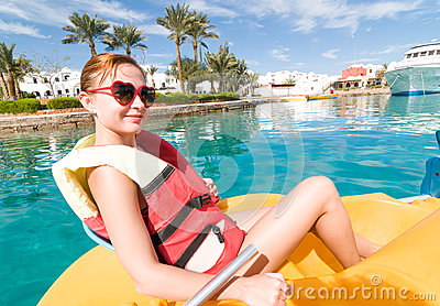 Red young woman riding catamaran