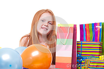 Redhead  girl with balloons and gift box