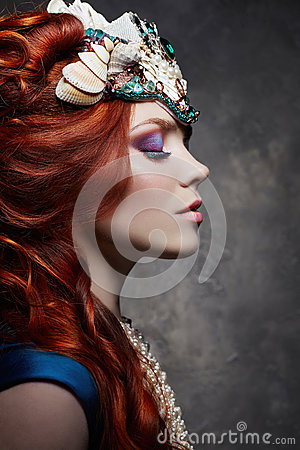 Redhead girl fabulous look, blue long dress, bright makeup and big eyelashes. Mysterious fairy woman with red hair. Big eyes Stock Photo