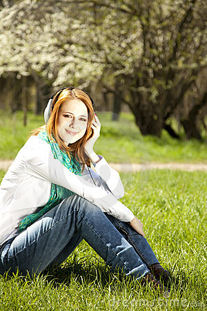 Redhead girl with headphone in the park