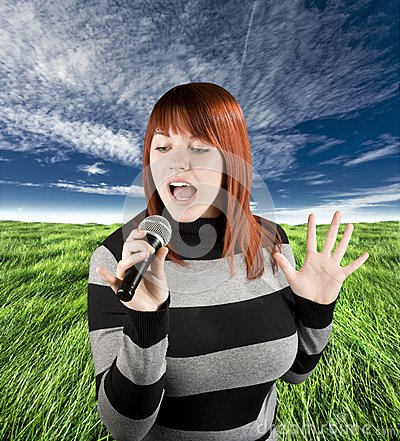 Redhead girl singing karaoke on microphone