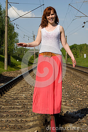 Redhead girl walks on the rails