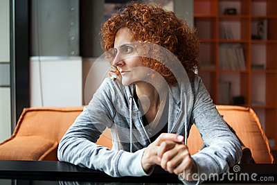 Redhead lady sitting at table