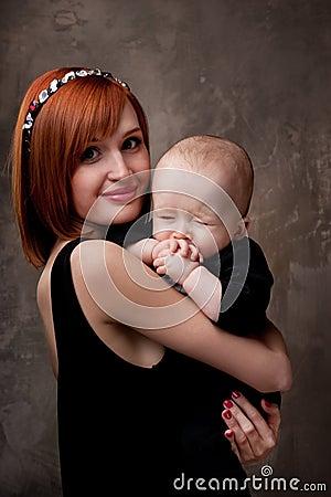 Redhead mother holding her sleepy baby boy