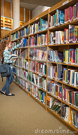 Redhead student taking a book from bookshelf in the library