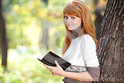 Redhead teenager woman reading a book