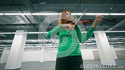 Redhead violinist speelt haar instrument in een hal stock footage