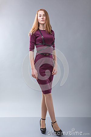 Free Redhead Woman In Burgundy Dress With Black Belt Standing In Photostudio On Gray Background Royalty Free Stock Image - 107738636