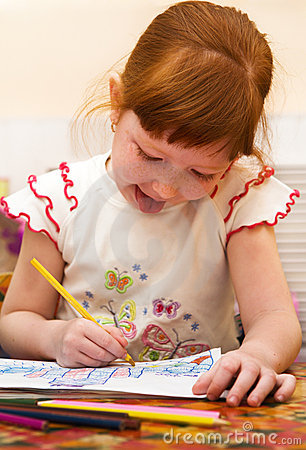 Redheaded child draws a picture