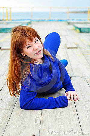 Redheaded girl laying on the pier