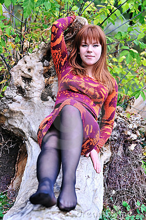 Redheaded girl resting in forest
