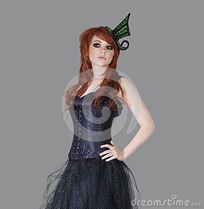 Redheaded teenage girl posing over gray background