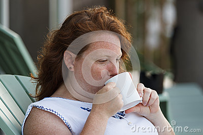 Redheaded woman drinking cup of coffee